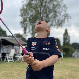 op deze foto zie je een jongen intens genieten van een badminton spel, iets wat je van je kinderen kunt leren